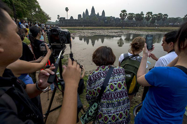 Tourists gather to watch and take pictures of Cambodia's world famous Angkor Wat temple during sunrise in Siem Reap on March 20, 2015. (Reuters photo)