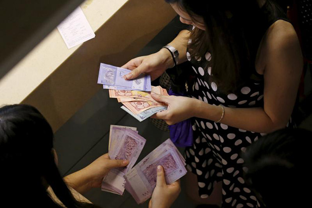 Customers count their ringgit notes outside a money changer at the central business district in Singapore on Aug 25, 2015. (Reuters photo)