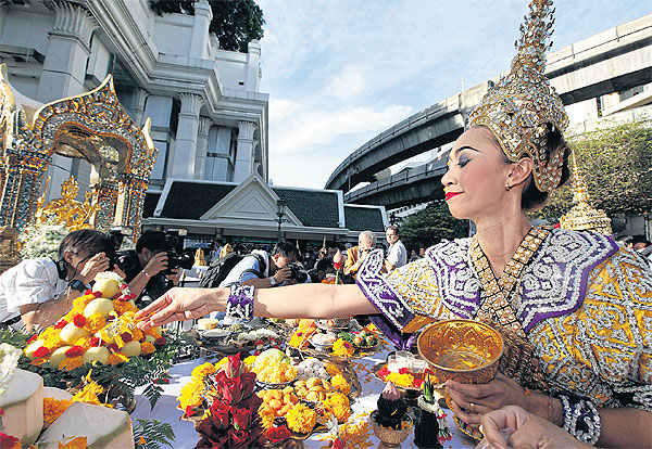 A traditional Thai dancer places flower offerings at the Erawan shrine to mark the end of repairs to the Brahma statue, damaged in the blast on Aug 17. (Photo by Apichart Jinakul)