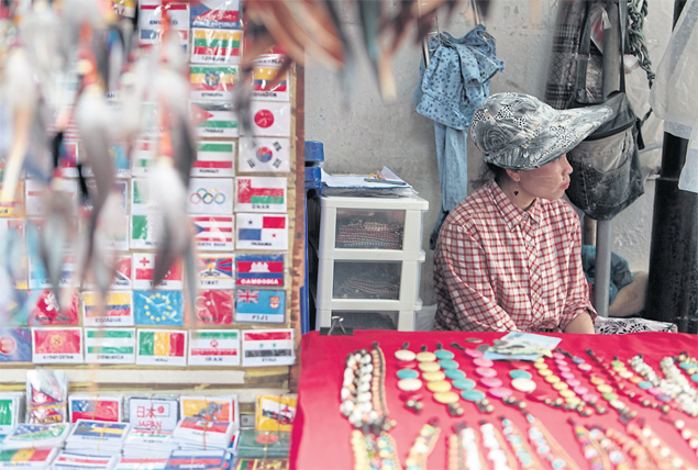A vendor waits for customers at a stall on Khao San Road. The central bank is expected to maintain its dovish monetary policy stance throughout the first half of next year to help the momentum of recovery.CHANAT KATANYU