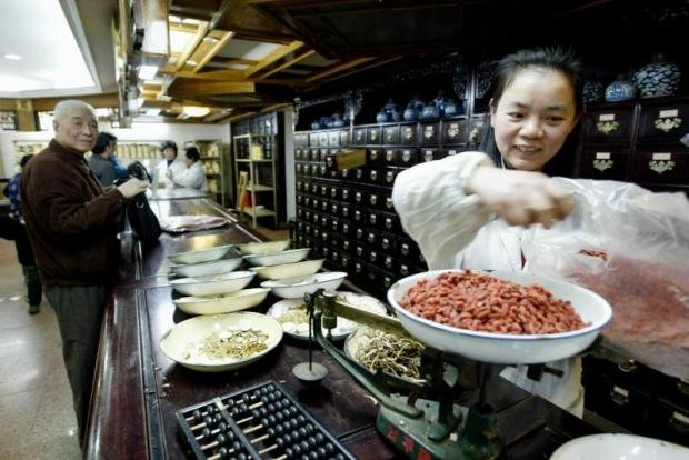 A saleswoman weighs some herbal ingredients for a customer in a traditional Chinese medicine pharmacy.(File photo)