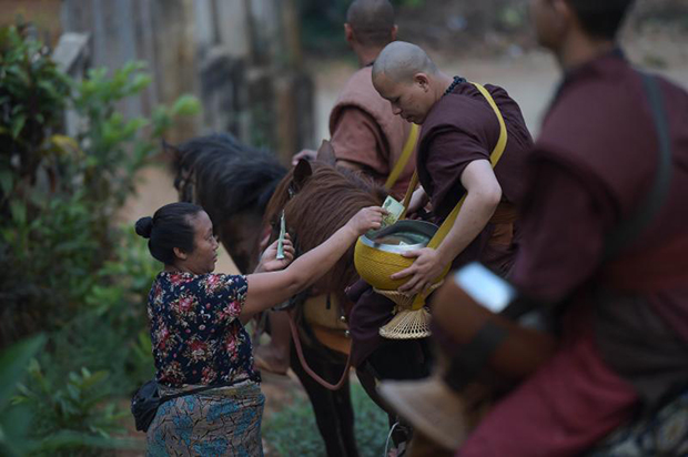 This picture taken on April 8, 2015 shows a resident offering alms to monks riding horses during their early morning alms-collecting round along the steep slopes surrounding the