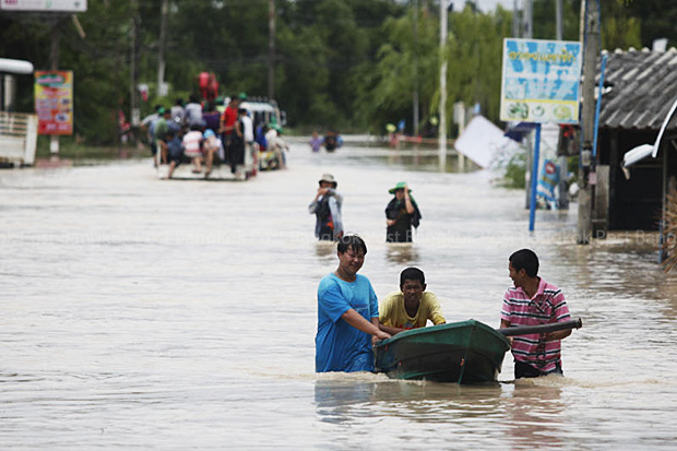 Villagers in tambon Tubma in Muang district in Rayong province use boats for transport on Friday after flooding hit their villages. (Photo by Pattarapong Chatpattarasill)