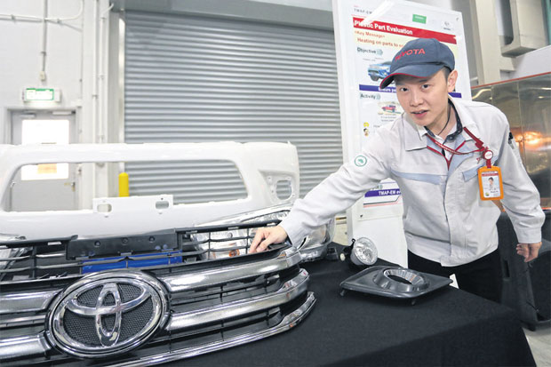 A technician at Toyota Motor Thailand shows reporters a new model of a plastic fender for the Toyota Hilux Revo at the company's factory in Samut Prakan's Bang Bo district.