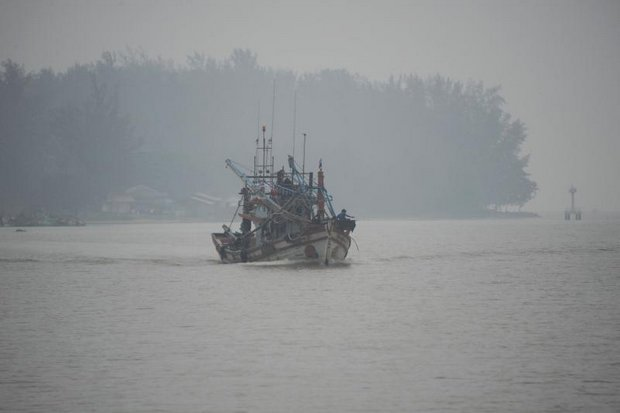 A fishing boat navigates the Narathiwat River on Tuesday. Prime Minister Prayut Chan-o-cha says fighting the haze problem is difficult because slash-and-burn agriculture is ingrained. (AFP photo)
