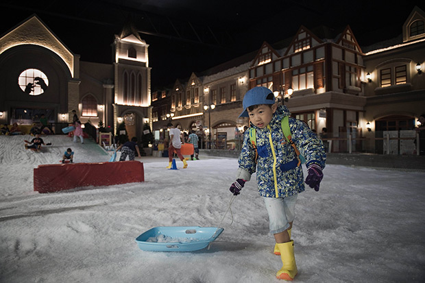 This August file photo taken shows a boy pulling his sledge at Snow Town in Bangkok. Across the notoriously sweltering metropolis, locals are flocking to a growing number of attractions offering Thais the chance to experience something few ever witness at home -- snow and ice. (AFP photo)