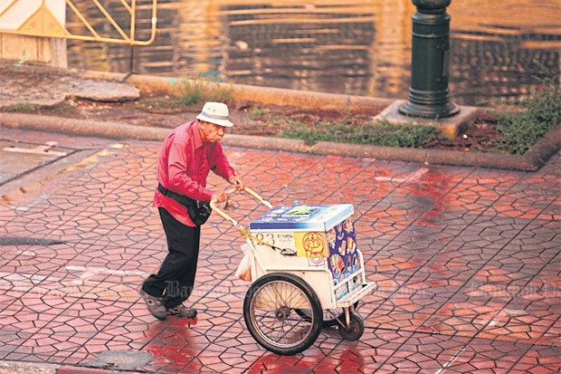 A vendor pushes an ice-cream cart near the Kasatsuek intersection in Bangkok. The lacklustre economy resulted in even lower consumer sentiment in last month's survey by the University of the Thai Chamber of Commerce. (Photo by Panupong Changchai)