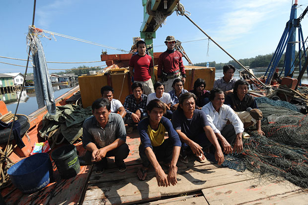 Eleven Vietnamese crewmen squat aboard one of the two modified boats seized for illegally fishing in Thai waters off Narathiwat on Saturday. (Photo by Waedao Harai)