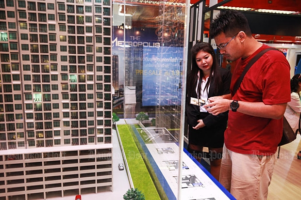 A potential buyer checks prices of units at a house and condominium fair at Queen Sirikit National Convention Center on Thursday. (Photo by Panupong Changchai)