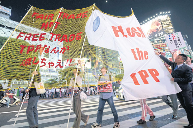 A banner protesting the Trans-Pacific Partnership (TPP) trade agreement is paraded through Shibuya district of Tokyo. (Bloomberg photo)