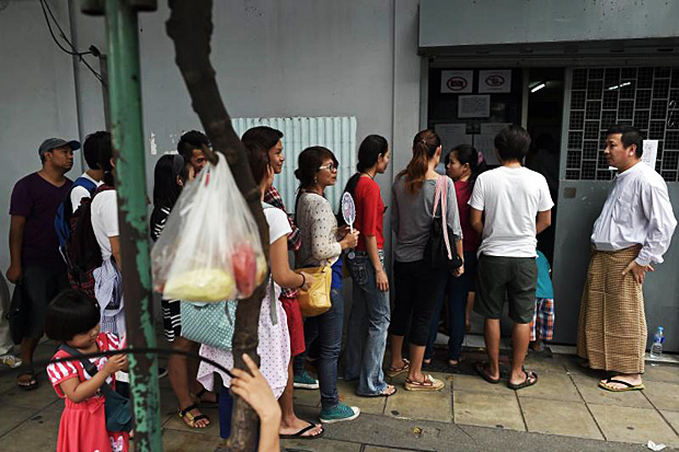 An official (right) stands outside the Myanmar embassy in Bangkok as Myanmar nationals living in Thailand queue up before casting their vote for the Nov 8 election on Saturday. (AFP photo)