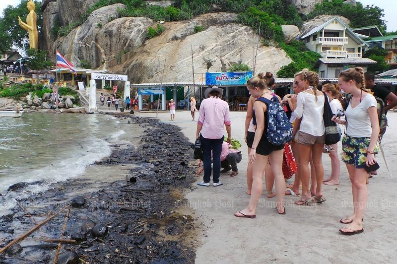 Tourists look at the ugly mixture of oil and garbage washed up at Chaiwat Satyaem beach, Hua Hin, Oct 27 2015 (Post Today photo)
