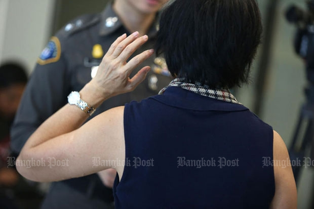 A woman victim explains to a Crime Suppression Division officer how an online scammer, said to be part of an African gang, tricked her into transferring money into his account. (Photo by Pattanapong Hirunard)