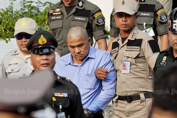 Police escort suspect Suriyan Sucharitpolwong to the military court on Oct 21 to seek an order for his detention for 12 days. (Photo by Krit Promsaka na Sakolnakorn)