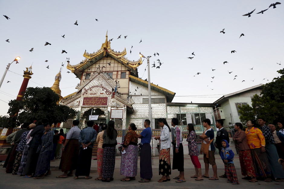 People line up outside a Buddhist prayer hall to vote during the general election in Mandalay. - Reuters