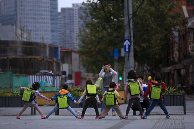 Kindergarten children pose for a picture on a street in Shanghai. (Reuters photo)
