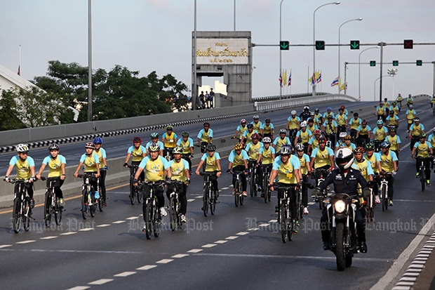 """Cyclists make their way across Phra Pinklao Bridge on Nov 8 as still pictures and video are captured to produce promotional material for the """"Bike for Dad"""" event on Dec 11 to commemorate His Majesty the King's birthday. (Photo by Wichan Charoenkiatpakul)"""