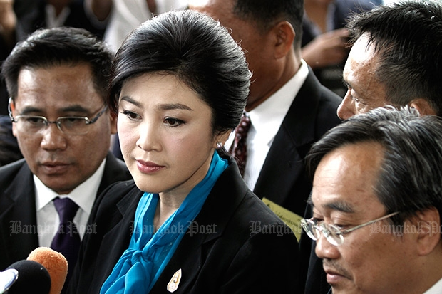 Former prime minister Yingluck Shinawatra speaks to reporters outside the Supreme Court in August. (Photo by Pattanapong Hirunard)