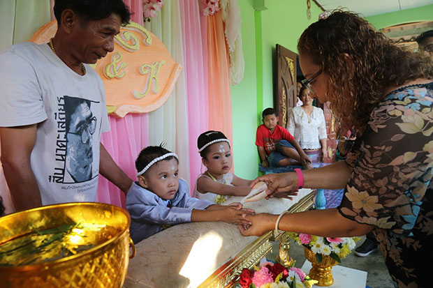 A guest pours holy water from a conch shell onto the hands of the four-year-old