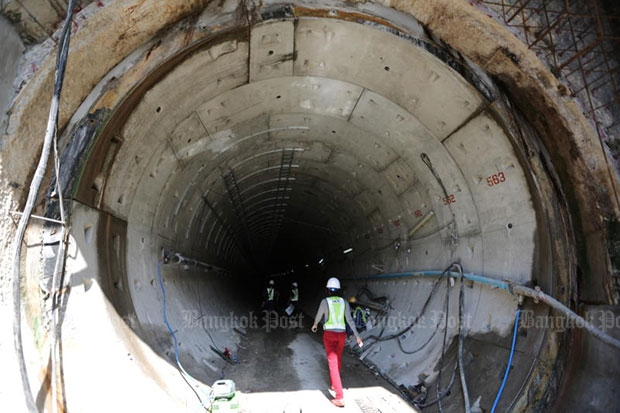 A worker walks into an underground tunnel at the construction site for a mass-transit route under the Chao Phraya River on Wednesday. (Photo by Pattanapong Hirunard)