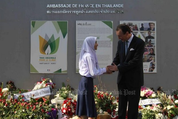 French ambassador Gilles Garachon thanks a Thai schoolgirl for her condolences at a makeshift memorial at the base of the embassy's wall in Bang Rak district. (Photo by Somchai Poomlard)