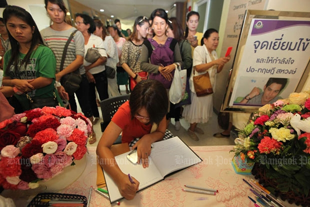 Well-wishers sign a get-well book for actor Tridsadee 'Por' Sahawong at Ramathibodi Hospital where he is being treated for dengue fever. (Bangkok Post file photo)