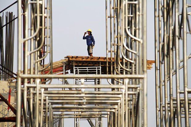 A worker stands on scaffolding at the site of a new highway under construction in east Jakarta, Indonesia, Nov 4, 2015. (Reuters photo)