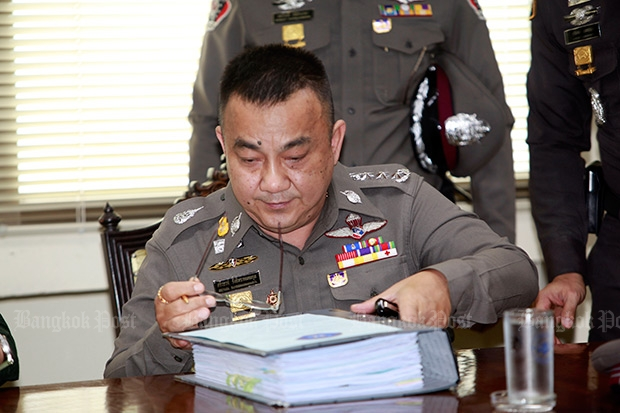 """Deputy national police chief Srivara Rangsibrahmanakul looks at the investigative report for lese majeste suspsect Suriyan """"Mor Yong"""" Sucharitpolwong on Friday. Pol Gen Srivara said Wednesday more arrest warrants have been sought in the widening case. (Photo by Apichart Jinakul)"""