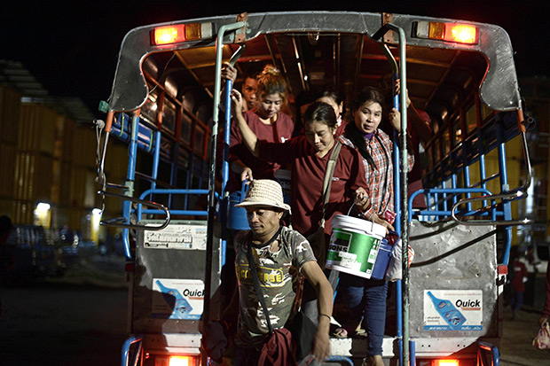Men and women exit a truck as they come back from work to a construction workers' camp made of steel containers in Samut Prakan. (AFP photo)