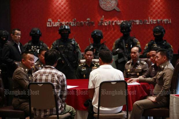 Senior officers talk to two suspects at the Royal Thai Police Office in Bangkok on Thursday during a press conference on the suspected
