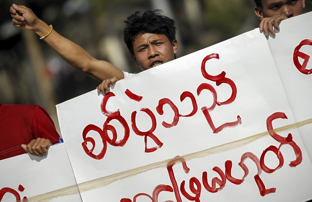 A demonstrator holds a placard saying
