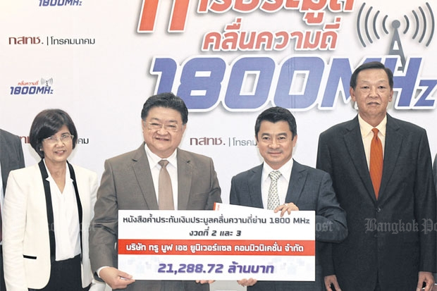 Thiti Nantapatsiri, True group executive director (second left) and Col Settapong Malisuwan, NBTC vice-chairman, hold the symbolic cheque representing two bank guarantees totalling 21.3 billion baht handed over by TMC yesterday. Flanking them are Wilaiwan Srisamrual, True chief financial officer for mobile business group (left) and Gen Sukij Kamasunthorm, an NBTC commissioner.