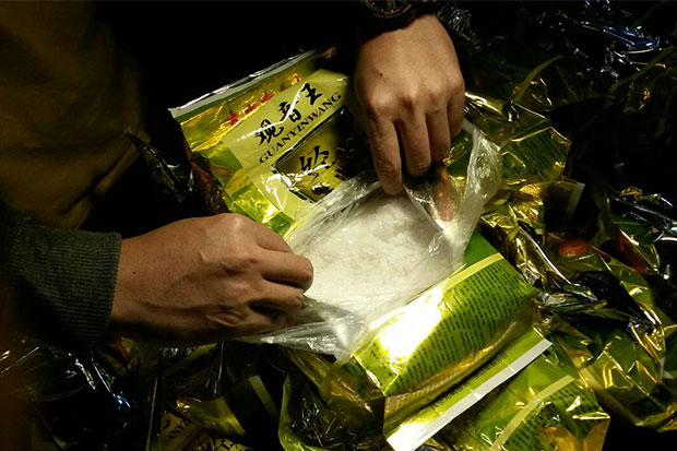 Crystal methamphetamine is found in tea packages abandoned by fleeing drug traffickers in front of a store in Mae Sai district of Chiang Rai on Friday evening. (Photo by Chinpat Chaimon)