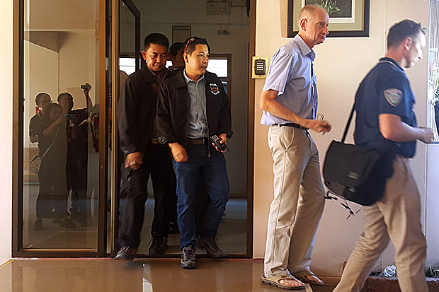 Convicted Australian paedophile Peter Dundas Walbran, blue shirt, is led away by police after a search of his Ubon Ratchathani home. (Photo by Dusit Singkhiri)