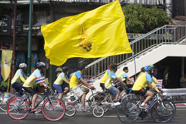 Cyclists with a flag of His Majesty the King flag ride past Wong Wian Yai, the site of the King Taksin the Great Monument, in Bangkok on Friday. (Photo by Pawat Laopaisarntaksin)