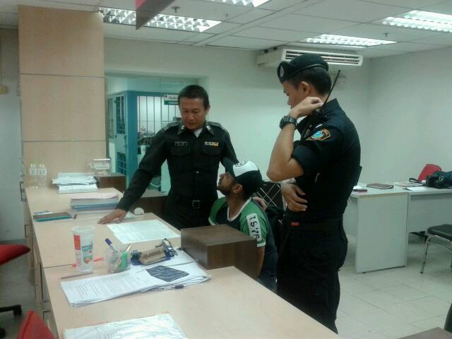 Police officers at Suvarnabhumi airport interrogate Reto Steinacher on Friday after removing him from a Bangkok Airways flight following a bomb threat. (Photo by Sutthiwit Chayutworakan)
