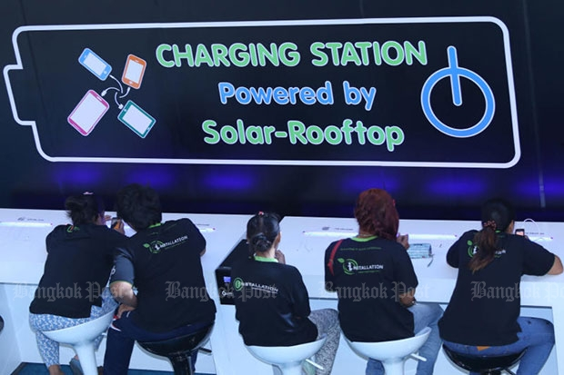 People are playing with their phones while waiting for charging up battery at 'Solar Charger Station'. The station provide free phone battery charge for every attendants at Queen Sirikit Centre on February 24, 2015. (Bangkok Post file photo)