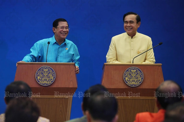 Prime Minister Prayut Chan-o-cha and Cambodian Premier Hun Sen smile while taking questions from reporters after a joint cabinet meeting at Government House on Saturday. (Photo by Thiti Wannamontha)