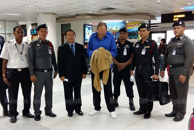Peter Effers (blue shirt) is detained after a pre-boarding search allegedly found 1.6kg of heroin strapped around his waist at Phuket airport on Wednesday morning. (Photos by Achadtaya Chuenniran)
