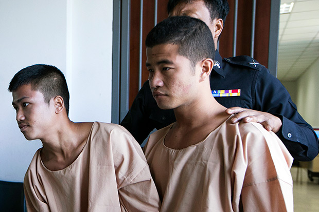 Myanmar migrants Win Zaw Htun, right, and Zaw Lin, left, both 22, are escorted by officials after their guilty ruling at court in Koh Samui Dec 24. The court on Thursday sentenced the two Myanmar migrants to death for killing British backpackers David Miller, 24, and Hannah Witheridge, 23, on Koh Tao last year. (AP photo)