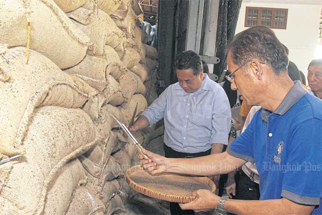 Commerce Ministry officials examine the quality of pledged rice in a warehouse in Nakhon Pathom province. The government is considering a transfer of the 500 billion baht in BAAC debt accumulated from rice-pledging schemes to the fiscal ledger. TAWATCHAI KEMGUMNERD