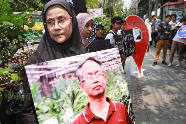 Angkhana Neelapaijit holds a picture of her missing husband, Somchai, on the 11th anniversary of his disappearance from Ramkhamhaeng Soi 69, where he was last seen on March 12, 2004. (Photo by Somchai Poomlard)
