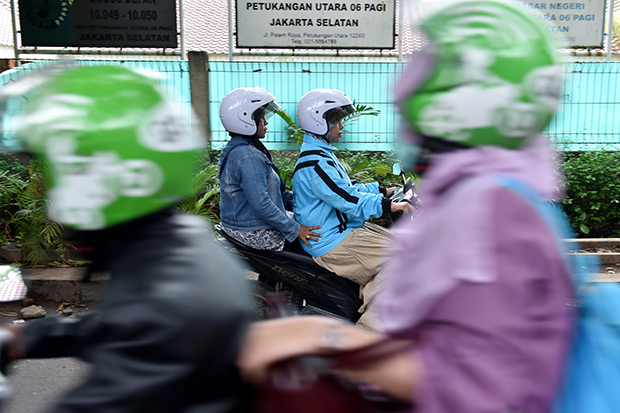 This picture taken on Nov 22 shows a female motorcycle taxi driver (centre right) travelling with a passenger in Jakarta. A flurry of new motorbike taxi options have in the past year appeared in the metropolis of 10 million, giving Indonesia's growing middle class a greater choice of transport to get through some of the world's worst traffic jams. (AFP photo)