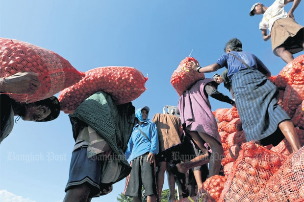 Workers load red onions onto a barge docked at Moei River on the Myanmar bank. Border trade. PATTARACHAI PREECHAPANICH