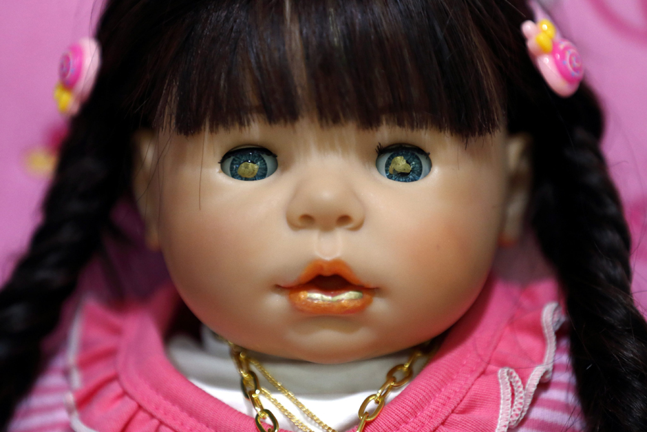 The picture shows a Child Angel doll painted with holy gold sheets in its eyes and mouth. They were applied by Buddhist monks during a ritual in Bangkok.