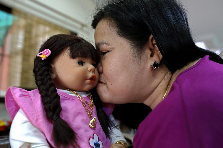Thai devotee Ratchada Mahanavanont, 45, kisses her Child Angel doll at her house in Bangkok.