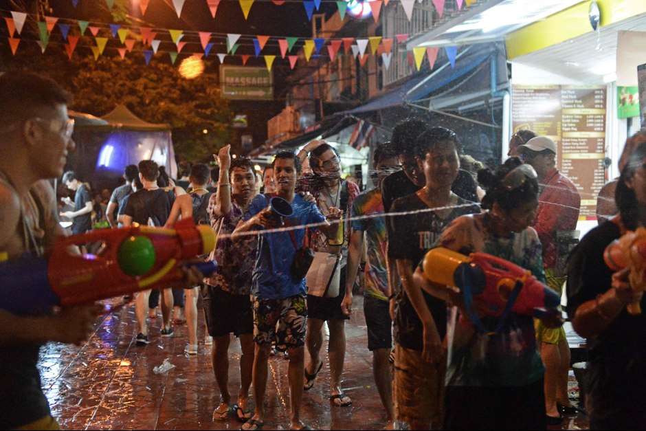 Revellers engage in a water fight during Songkran on Khao San Road on Thursday night. - AFP