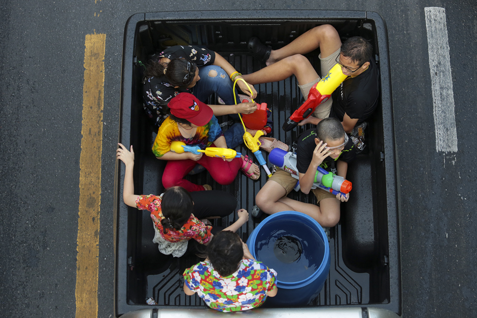 Adults and children armed with water guns cram into the back of a pickup truck on Charoen Krung Road, Bangkok. This year, the government outlawed water-splashing from pickups and other vehicles from 10am-7pm in specific areas. - Patipat Janthong