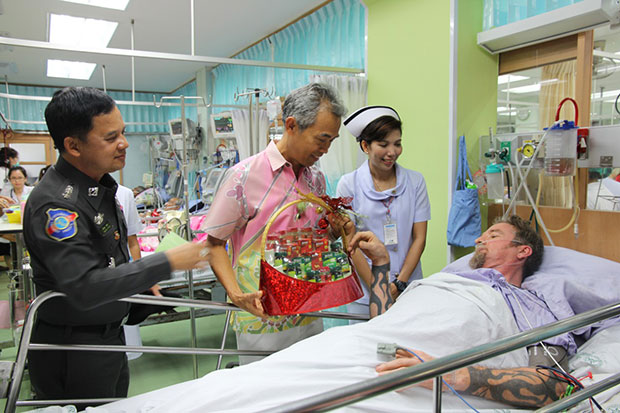 Nurse Srikanya Chuerob, 39, right, visits Gunter Retsch at Surat Thani Hospital on Sunday. Surat Thani deputy governor Ouaychai Innak, centre, and Pol Lt Col Akkharapol Ponsa, a tourist police inspector, left, were also there to wish him a speedy recovery.  (Photo by Supapong Chaolan)
