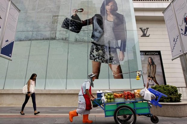 A fruit vendor pushes his cart past a luxury mall near the Erawan shrine. (EPA photo)
